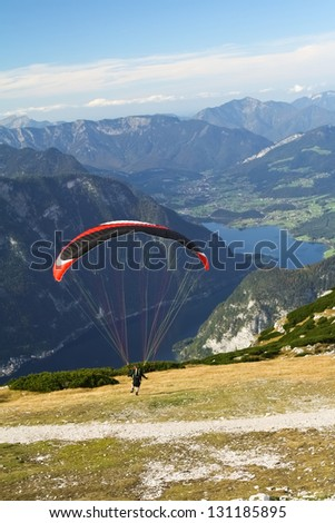 Paragliding above mountain lake Hallstattersee in Alps - stock photo