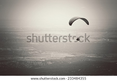 Paragliding, flying over El Escorial in Madrid, Spain. Black and white picture. - stock photo