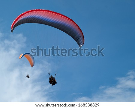 Paragliding in tandem against clear blue sky extreme sport background image - stock photo