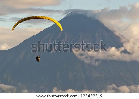 PARAGLIDING OVER TUNGURAHUA VOLCANO IN ECUADOR, AERIAL VIEW  - stock photo