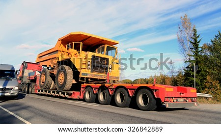 PARAINEN, FINLAND - OCTOBER 9, 2015: Volvo FH hauls a Volvo BM 540 Rigid dump truck as wide load. The BM 540 was designed a cost-effective load carrier for construction and mining. - stock photo