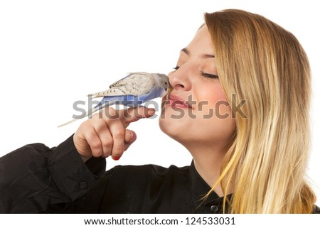 Parakeet sitting on womans finger and she gives the bird a little kiss. - stock photo