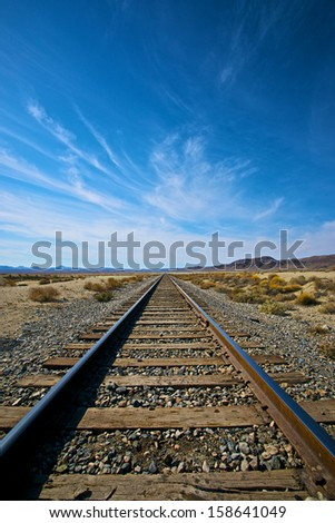 Parallel railroad tracks in the Mojave Desert of California lead into the distance.  - stock photo