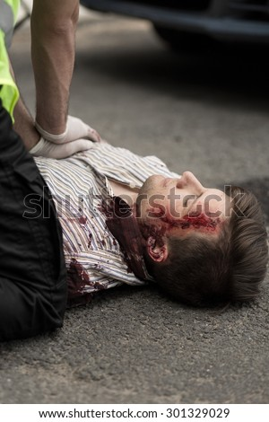 Paramedic applying first aid victim of car crash - stock photo