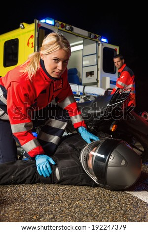 Paramedic assisting injured motorbike man driver on road at night - stock photo