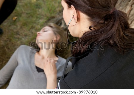 Paramedic checking vitals on an injured woman in a park.  Shallow depth of field, focus on paramedic - stock photo