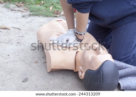 Paramedic practicing Cardiopulmonary resuscitation - CPR on a dummy - stock photo
