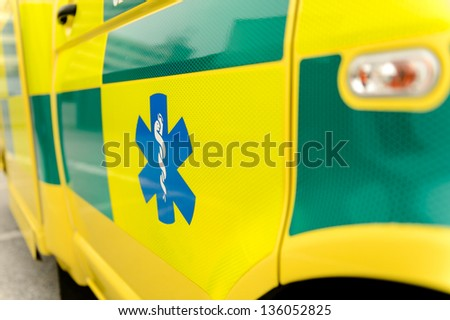 Paramedic symbol on yellow ambulance car - stock photo