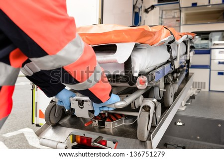 Paramedic taking out stretcher from ambulance car - stock photo