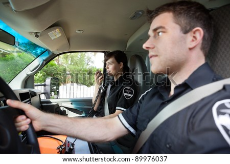 Paramedic talking on radio to dispatcher.  Shallow DOF critical focus on woman with handset - stock photo