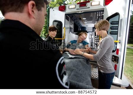 Paramedic team placing senior woman in ambulance, caregiver at side - stock photo