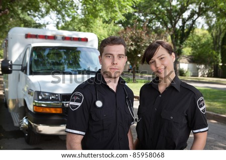 Paramedic team portrait with ambulance in background - stock photo
