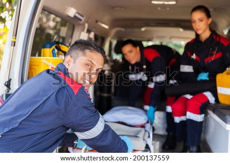 paramedic team pulling stretcher out of an ambulance - stock photo