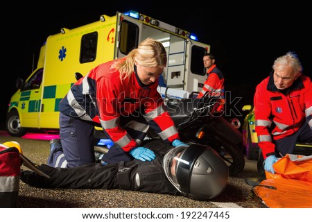 Paramedical team assisting injured man motorbike driver at night - stock photo