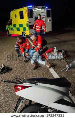 Paramedics assisting injured motorbike woman driver lying on road night - stock photo