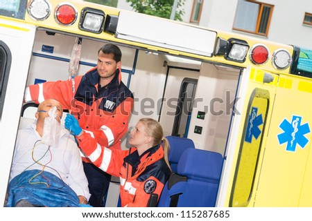 Paramedics checking IV drip patient in ambulance treatment aid emergency - stock photo