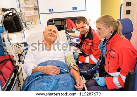 Paramedics checking patient pulse in emergency car ambulance medical chart - stock photo