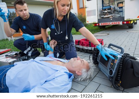 Paramedics checking pulse of unconscious senior man lying on street - stock photo