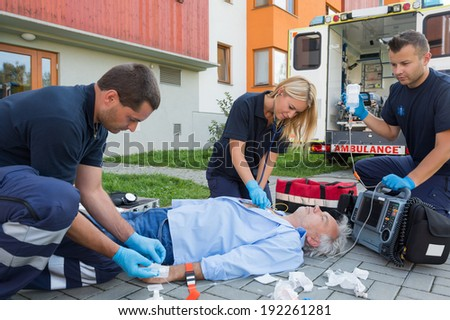 Paramedics giving firstaid to unconscious senior patient lying on ground - stock photo
