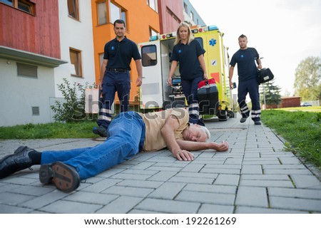 Paramedics giving help to injured senior man lying on street - stock photo