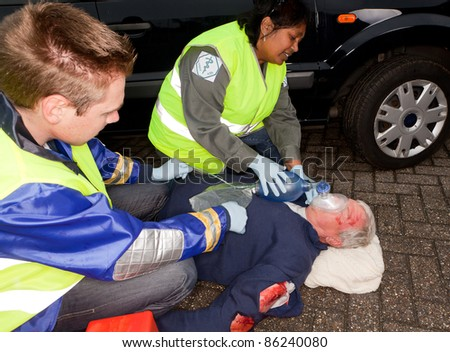 Paramedics helping a car crash victim with an oxygen mask (sleeve badges have been replaced by a non exisiting logo) - stock photo