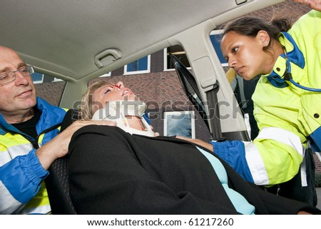 Paramedics placing a neck brace on an injured woman inside her car after a car crash