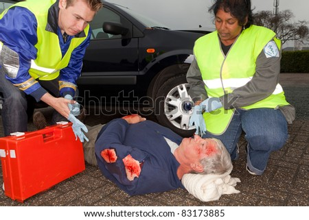 Paramedics putting on sterile gloves to care for a car crash victim  (the sleeve badges have been replaced by a non existing logo) - stock photo
