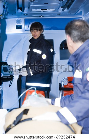 Paramedics taking woman on stretcher into the ambulance With Patient - stock photo