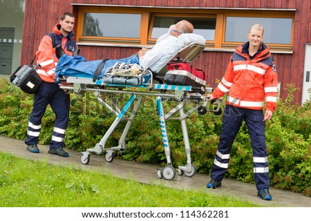 Paramedics with patient on emergency stretcher ambulance aid woman man - stock photo