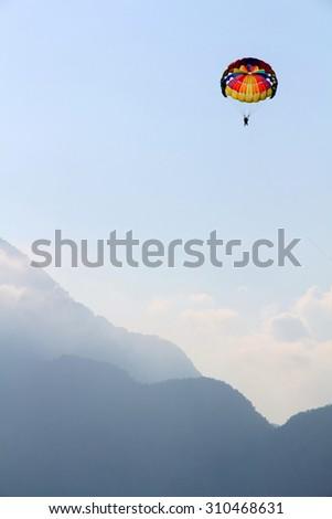 Parasailing in a blue sky near sea beach - stock photo