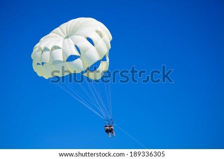 Parasailing under blue sky. - stock photo