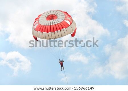 Parasailing under blue sky and white clouds - stock photo