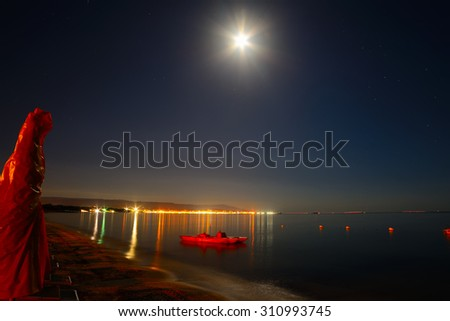 parasol and boat on a starry night in Alghero, Sardinia - stock photo