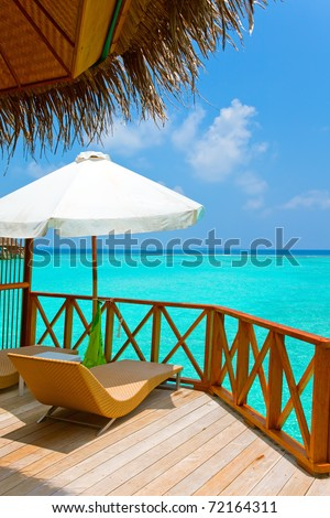 Parasol and chaise lounges on a terrace of water villa, Maldives. - stock photo