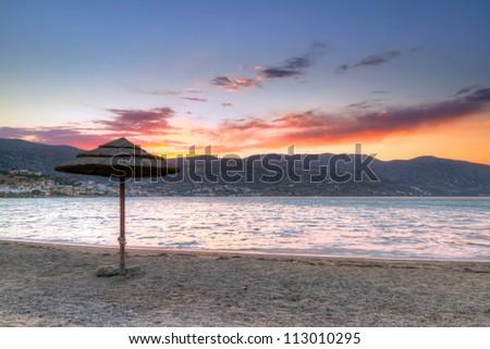 Parasol at Mirabello Bay at sunset, Greece - stock photo