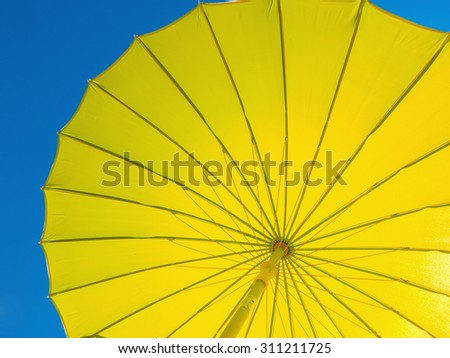 Parasol in yellow against the sky. Sun protection in summer - stock photo