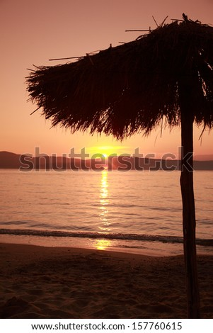 Parasol sunset, Ag Paraskevi beach, Skiathos, Greece  - stock photo