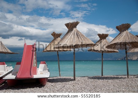 parasols an a pedal boat on the beach in the mediterranean - stock photo