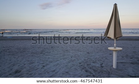 parasols and deck chairs on the beach ar rimini on adriatic sea in italy at sunset