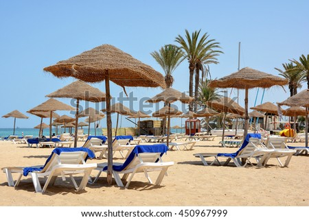 Parasols and sun loungers on a sandy beach in Sousse.Tunisia