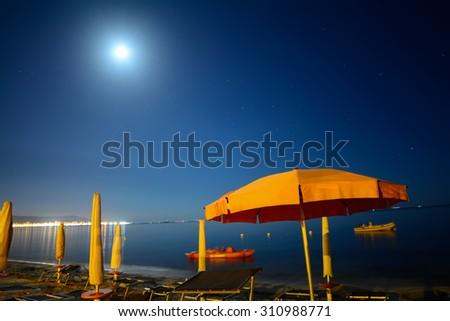 parasols by the sea under a bright moon, Sardinia - stock photo