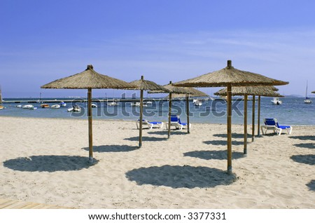parasols on an empty beach with a beautiful blue sky