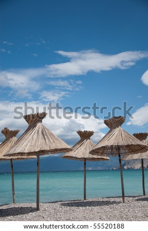 parasols on the beach in the mediterranean - stock photo
