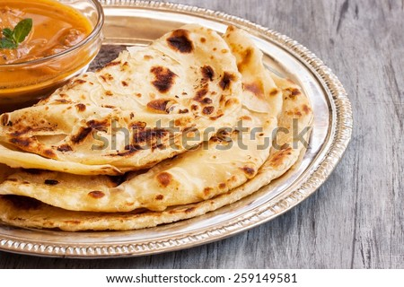 Paratha served with chicken curry close up selective focus - stock photo