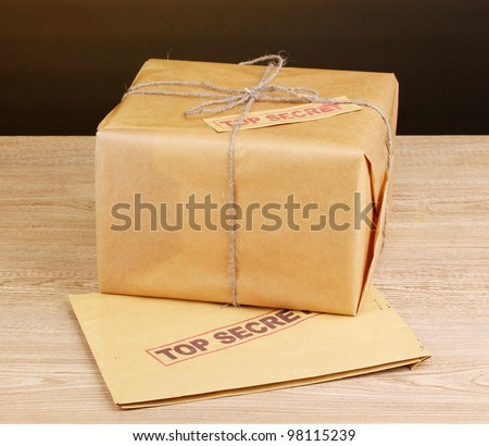 Parcel and envelope with top secret stamp on wooden table on brown background - stock photo