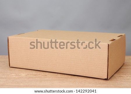 Parcel box on wooden table, on grey background - stock photo