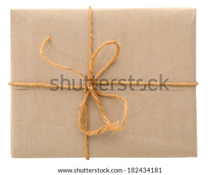 Parcel wrapped in brown paper and tied with rough twine, above view - stock photo