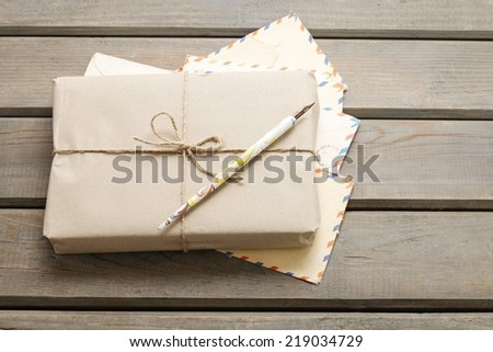 Parcel wrapped with brown paper on a wooden table - stock photo