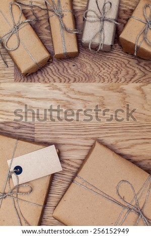 Parcels and boxes in eco paper on the wooden table. Top view. Boxes for gifts tied with twine. - stock photo