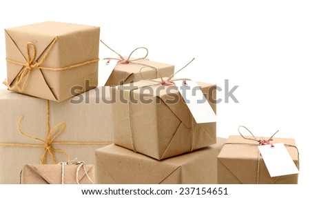 parcels in brown wrapping paper and blank tags or labels isolated on white background  - stock photo